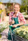 La mujer sonriente del centro de jardinería florece el pulgar para arriba Foto de archivo