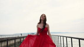 La mujer sonriente despreocupada está caminando sobre el muelle, agitando su vestido rojo de seda almacen de metraje de vídeo