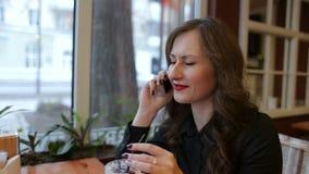 La mujer sonriente en café está hablando con el teléfono móvil almacen de metraje de vídeo