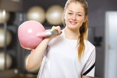 La mujer sonriente en equipo del entrenamiento lleva a cabo el kettlebell en el gimnasio de la aptitud Imagen de archivo