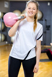 La mujer sonriente en equipo del entrenamiento lleva a cabo el kettlebell en el gimnasio de la aptitud Fotografía de archivo libre de regalías