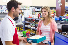 La mujer sonriente en la caja registradora que paga con la tarjeta de crédito y explora un producto Imagen de archivo