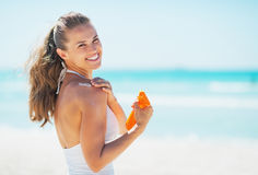 La mujer sonriente en la playa que aplica el sol bloquea la nata Foto de archivo libre de regalías