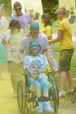 La mujer sonriente en la silla de ruedas cubierta con color amarillo saca el polvo Foto de archivo libre de regalías