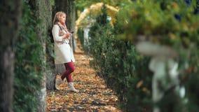La mujer sonriente en otoño parquea el mensaje que mecanografía en el teléfono móvil almacen de metraje de vídeo