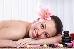 La mujer sonriente en salón del balneario, empiedra masaje Fotos de archivo