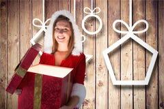 La mujer sonriente en santa viste la apertura de su caja de regalo contra fondo de madera Foto de archivo