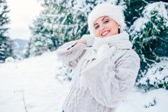 La mujer sonriente en sombrero acogedor del jersey que hace punto y de piel permanece el wint de OM Imagenes de archivo