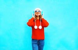 la mujer sonriente en suéter rojo, escucha la música en auriculares inalámbricos Foto de archivo