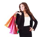La mujer sonriente en traje sostiene bolsos y mira lejos Imagenes de archivo
