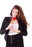 La mujer sonriente en traje sostiene la rosa del rojo Fotografía de archivo
