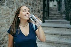 La mujer sonriente en una camiseta azul bebe el agua de la botella plástica Imagen de archivo libre de regalías