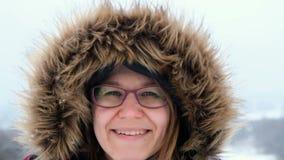 La mujer sonriente es nieve feliz y que sopla en la naturaleza del invierno almacen de video