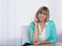La mujer sonriente está llamando por teléfono en la oficina Foto de archivo libre de regalías
