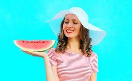la mujer sonriente está llevando a cabo una rebanada de sandía en un sombrero de paja Fotografía de archivo libre de regalías
