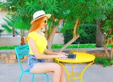 la mujer sonriente está trabajando usando un ordenador portátil se sienta en un café Fotografía de archivo