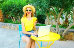 la mujer sonriente está trabajando usando un ordenador portátil se sienta en un café Fotografía de archivo libre de regalías