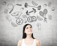 La mujer sonriente está pensando en su opción de la actividad del deporte Los iconos del deporte se dibujan en el muro de cemento Fotos de archivo libres de regalías