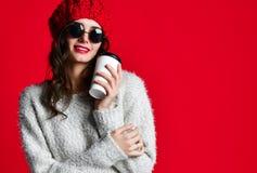 La mujer sonriente feliz de la moda sostiene la taza de café en fondo rojo de la pared foto de archivo