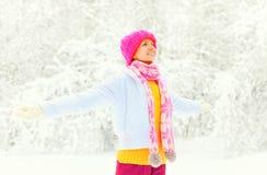 La mujer sonriente feliz del invierno de la moda que lleva la bufanda hecha punto colorida del sombrero goza sobre fondo nevoso Foto de archivo libre de regalías