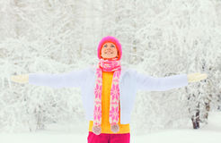 La mujer sonriente feliz del invierno de la moda que lleva la bufanda hecha punto colorida del sombrero goza sobre nevoso Fotos de archivo libres de regalías