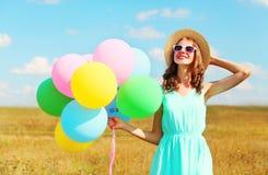 La mujer sonriente feliz del retrato con los globos coloridos de un aire está disfrutando de un día de verano en el cielo azul de Fotografía de archivo