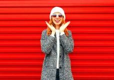 La mujer sonriente feliz del retrato de la moda ríe en fondo rojo Foto de archivo