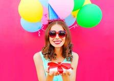 La mujer sonriente feliz del retrato en un casquillo del cumpleaños sostiene una caja de regalo en sus manos sobre un rosa colori Foto de archivo