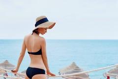 La mujer sonriente feliz en bikini y el sunhat en el mar varan fotografía de archivo