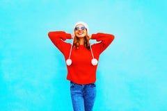La mujer sonriente feliz en rojo hizo punto el suéter y el sombrero en un azul Imagenes de archivo
