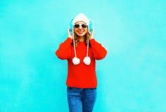 La mujer sonriente feliz en suéter rojo, escucha la música en auriculares inalámbricos Imágenes de archivo libres de regalías