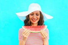 La mujer sonriente feliz está llevando a cabo una rebanada de sandía en un sombrero de paja Imagen de archivo libre de regalías