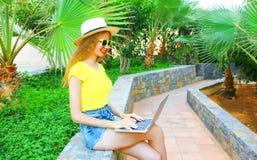 La mujer sonriente feliz está trabajando usando un ordenador portátil Imágenes de archivo libres de regalías