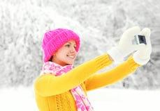 La mujer sonriente feliz hace el autorretrato en smartphone en invierno Imágenes de archivo libres de regalías