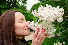 La mujer sonriente feliz que escucha el aroma del blanco joven de la lila florece en parque de la primavera Imagen de archivo libre de regalías