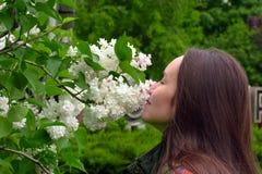 La mujer sonriente feliz que escucha el aroma del blanco joven de la lila florece en parque de la primavera Imagenes de archivo