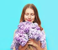 La mujer sonriente feliz que goza del olor de la lila del ramo florece imagen de archivo