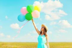 La mujer sonriente feliz sostiene un aire que los globos coloridos están disfrutando de un día de verano en el cielo azul del pra Imagen de archivo