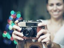 La mujer sonriente fotografió la cámara retra Imagen de archivo