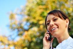 La mujer sonriente habla en el teléfono móvil con el copia-espacio Imagen de archivo