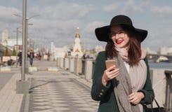 La mujer sonriente hermosa en vidrios lleva el equipo de moda usando la multitud Imagen de archivo