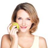 La mujer sonriente hermosa joven toca la manzana para hacer frente. Fotografía de archivo