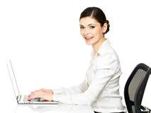 La mujer se sienta de la tabla y del trabajo en el ordenador portátil Imagen de archivo