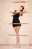La mujer sonriente hermosa se sostiene en la escalera de cuerda de bambú Foto de archivo