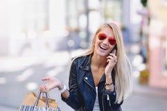 La mujer sonriente joven con los panieres habla por el teléfono portátil Fotos de archivo libres de regalías