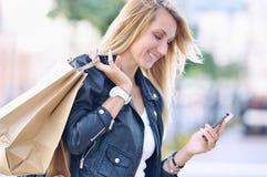 La mujer sonriente joven con los panieres leyó algo en smartphone Foto de archivo libre de regalías
