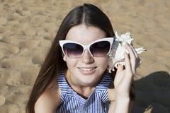 La mujer sonriente joven escucha una concha marina Fotografía de archivo libre de regalías