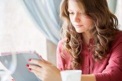 La mujer sonriente joven está bebiendo el café en un café Imágenes de archivo libres de regalías