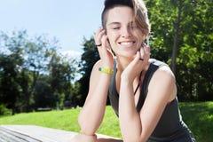 La mujer sonriente joven est? descansando sobre banco despu?s de activar en parque fotografía de archivo libre de regalías
