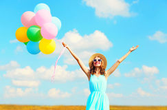 La mujer sonriente joven feliz con los globos coloridos de un aire está disfrutando de un día de verano en el cielo azul del prad Foto de archivo